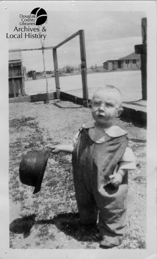 Image shows a baby about one year old. He is in overalls, wearing glasses and holding a man\\\'s top hat. He is in a yard and it is the 1920s or 1930s.