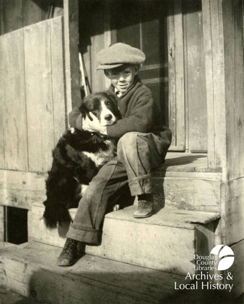 Image shows a young boy hugging a dog while sitting on wooden porch steps. He is wearing clothing from the 1920s or 1930s and the dog is a border collie mix. This image won the Archive Award for Goodest Boy or Cutest Animal.