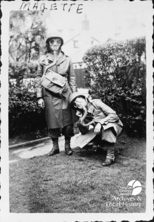 Image shows two nurses in gas masks and World War II combat gear. One woman is kneeling and one is standing. This image won the Archives Award for Coolest Nurses.