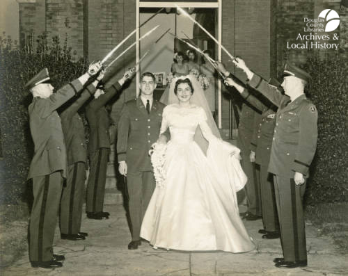 Image shows bride Joan Cooley and groom Andrew Cooley leaving their wedding ceremony under an arch formed by the sabers of an Honor Guard. This is the winner of the Archives Award for Best Wedding Dress.