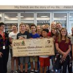Cimarron Middle School Principal Chris Zimmerman, left, and Library Specialist Carol Oliver were flanked by students in the school library to claim their summer reading contest winnings.