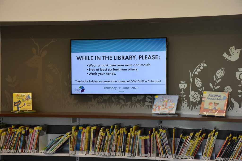 Digital screens prompt library customers to safeguard against the spread of COVID-19.