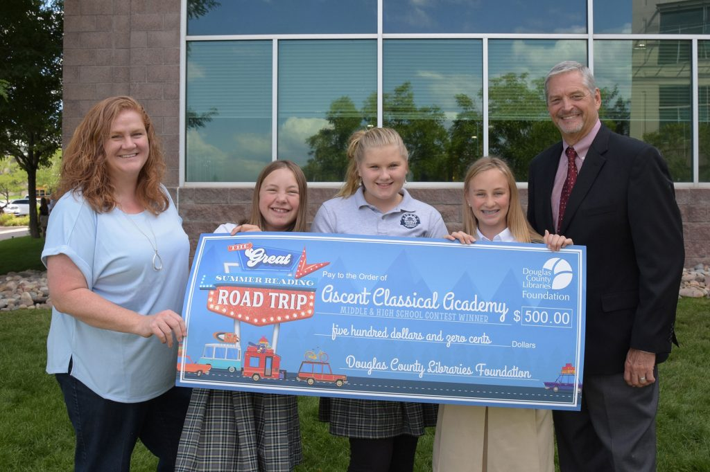 Ascent Classical Academy student representatives and Principal Dr. Don Griffin accepted their summer reading contest winnings in front of their school in Lone Tree.